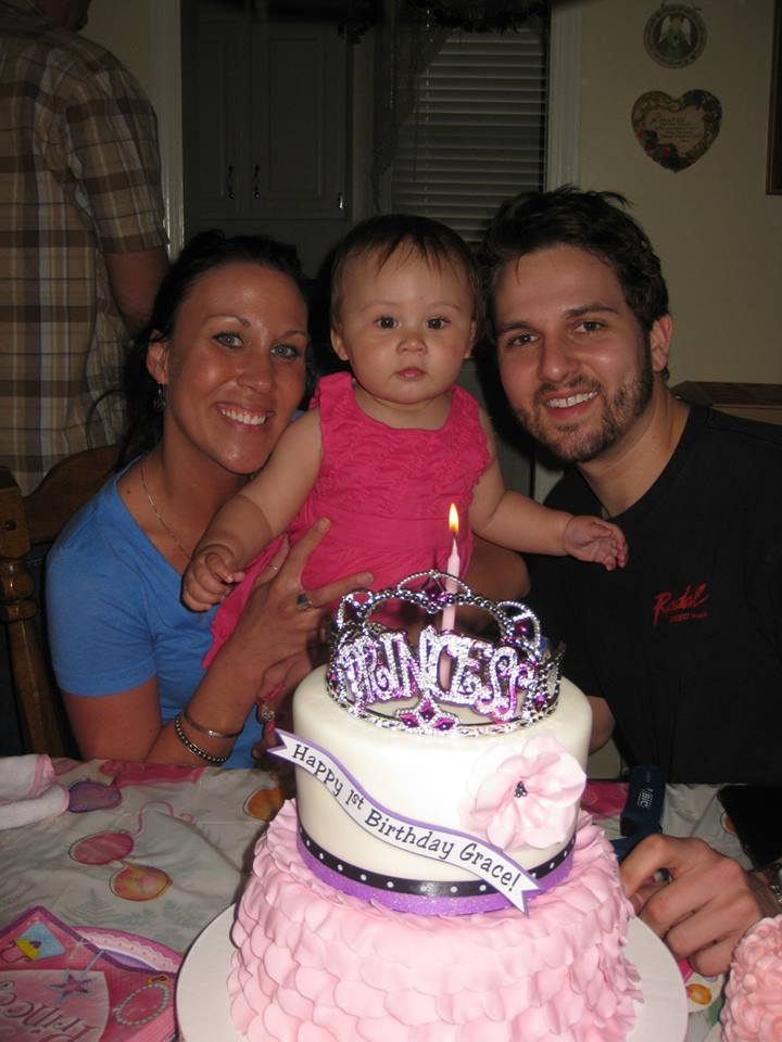 Grace with her mommy and daddy and her princess cake